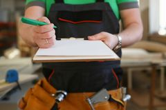 Arms of worker offer clipboard with green pen. Closeup. Manual job DIY inspiration improvement fix shop graphic joinery startup workplace idea designer career Stock Image