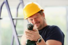 Arms of worker using electric drill closeup Royalty Free Stock Images