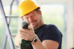 Arms of worker using electric drill closeup. Manual job DIY inspiration improvement fix shop yellow helmet joinery startup idea industrial education profession Royalty Free Stock Photos