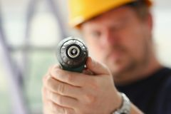 Arms of worker using electric drill closeup. Manual job DIY inspiration improvement fix shop yellow helmet joinery startup idea industrial education profession Royalty Free Stock Photography