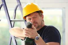 Arms of worker using electric drill closeup. Manual job DIY inspiration improvement fix shop yellow helmet joinery startup idea industrial education profession Stock Image
