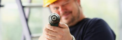 Arms of worker using electric drill closeup. Manual job, DIY inspiration, improvement, fix shop, yellow helmet, joinery startup idea, industrial education Stock Photography