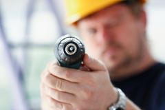 Arms of worker using electric drill closeup Royalty Free Stock Photos