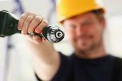 Arms of worker using electric drill closeup Royalty Free Stock Photo