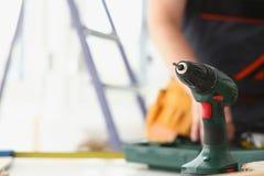 Arms of worker using electric drill. Closeup. Manual job DIY inspiration improvement job fix shop yellow helmet joinery startup idea industrial education Royalty Free Stock Photos