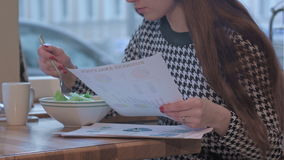 Arms of young businesswoman reading documents. She is sitting at the table in cafe and eating a salad stock footage