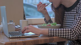 Arms of young businesswoman using a laptop for work. She is sitting at the table in cafe and eating a salad. Close up of arms of young businesswoman using a stock footage