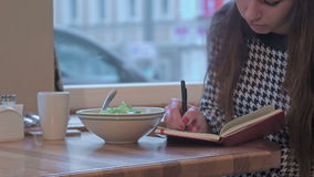 Arms of young businesswoman writing in note book. She is sitting at the table in cafe and eating a salad stock footage