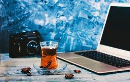 Armudu en verre de tulipe avec le thé sur la table en bois avec une rétro caméra noire et un ordinateur portable gris image libre de droits