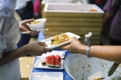 Armut in den armen Leuten der Gesellschaft hat Nahrung vom Philanthrop gespendet: Konzeptarmut und -spende: Freiwillig-Anteil stockfotos