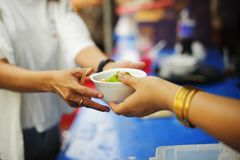 Armut in den armen Leuten der Gesellschaft hat Nahrung vom Philanthrop gespendet: Konzeptarmut und -spende: Freiwillig-Anteil lizenzfreie stockfotografie