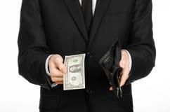 Armut und Geldthema: ein Mann in einem schwarzen Anzug, der eine leere Geldbörse und eine Banknote 1 Dollar auf Weiß hält, lokali Stockbilder