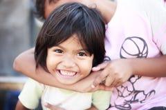 Armutkinder, die glücklich draußen in einem Dorf trotz des schlechten Lebens spielen lizenzfreie stockbilder