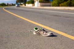 Armutkonzept - heraus geworfen auf den schmutzigen zackigen Turnschuh der Straße Lizenzfreie Stockfotografie