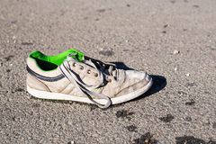 Armutkonzept - heraus geworfen auf den schmutzigen zackigen Turnschuh der Straße Lizenzfreies Stockbild