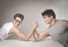Armwrestling. A very skinny guy is arm wrestling with a very muscular guy Royalty Free Stock Images