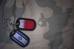 Army blank, dog tag with flag of bahrain and israel on the khaki texture background. Royalty Free Stock Images