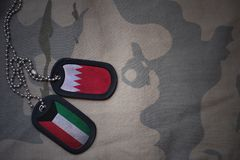 Army blank, dog tag with flag of bahrain and kuwait on the khaki texture background. Military concept Stock Image