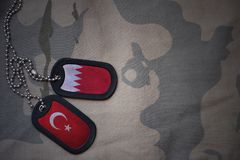 Army blank, dog tag with flag of bahrain and turkey on the khaki texture background. Military concept royalty free stock photography