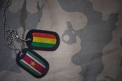 Army blank, dog tag with flag of bolivia and suriname on the khaki texture background. Military concept Stock Photos