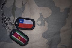 Army blank, dog tag with flag of chile and suriname on the khaki texture background. Military concept Stock Photography