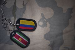 Army blank, dog tag with flag of colombia and suriname on the khaki texture background. Military concept Stock Image