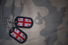 Army blank, dog tag with flag of georgia on the khaki texture background. Military concept Stock Images