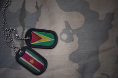 Army blank, dog tag with flag of guyana and suriname on the khaki texture background. Military concept Royalty Free Stock Images