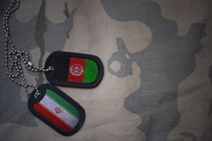 army blank, dog tag with flag of iran and afghanistan on the khaki texture background. Royalty Free Stock Photos