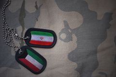 Army blank, dog tag with flag of iran and kuwait on the khaki texture background. Military concept Stock Image