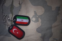 Army blank, dog tag with flag of iran and turkey on the khaki texture background. Military concept royalty free stock image