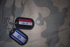 Army blank, dog tag with flag of iraq and israel on the khaki texture background. Royalty Free Stock Image