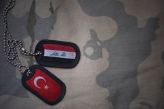 Army blank, dog tag with flag of iraq and turkey on the khaki texture background. Military concept stock photography