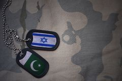 Army blank, dog tag with flag of israel and pakistan on the khaki texture background. Royalty Free Stock Photos