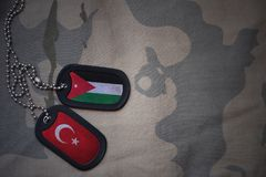 Army blank, dog tag with flag of jordan and turkey on the khaki texture background. Military concept royalty free stock photography