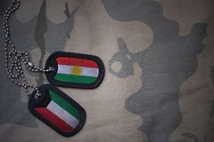 Army blank, dog tag with flag of kurdistan and kuwait on the khaki texture background. Military concept Stock Photography