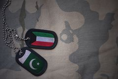 Army blank, dog tag with flag of kuwait and pakistan on the khaki texture background. Military concept Stock Images