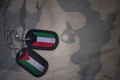 army blank, dog tag with flag of kuwait and palestine on the khaki texture background. Stock Photography