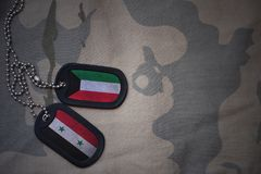Army blank, dog tag with flag of kuwait and syria on the khaki texture background. Military concept Royalty Free Stock Photography