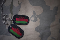 Army blank, dog tag with flag of malawi on the khaki texture background. Stock Photography