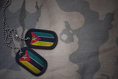 Army blank, dog tag with flag of mozambique on the khaki texture background. Stock Image