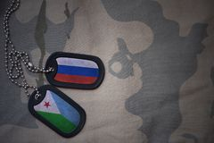 Army blank, dog tag with flag of russia and djibouti on the khaki texture background. Royalty Free Stock Photo