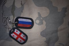 Army blank, dog tag with flag of russia and georgia on the khaki texture background. Military concept Royalty Free Stock Photos