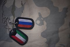 Army blank, dog tag with flag of russia and kuwait on the khaki texture background. Military concept Stock Image