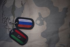 army blank, dog tag with flag of russia and libya on the khaki texture background. Stock Images