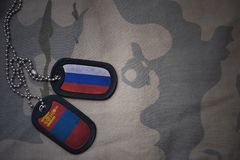 army blank, dog tag with flag of russia and mongolia on the khaki texture background. Stock Images