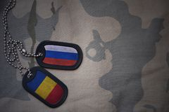 Army blank, dog tag with flag of russia and romania on the khaki texture background. Military concept Stock Image