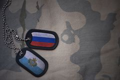 Army blank, dog tag with flag of russia and san marino on the khaki texture background. Royalty Free Stock Photography
