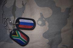 army blank, dog tag with flag of russia and south africa on the khaki texture background. Royalty Free Stock Images