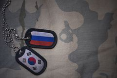 Army blank, dog tag with flag of russia and south korea on the khaki texture background. Military concept royalty free stock photography